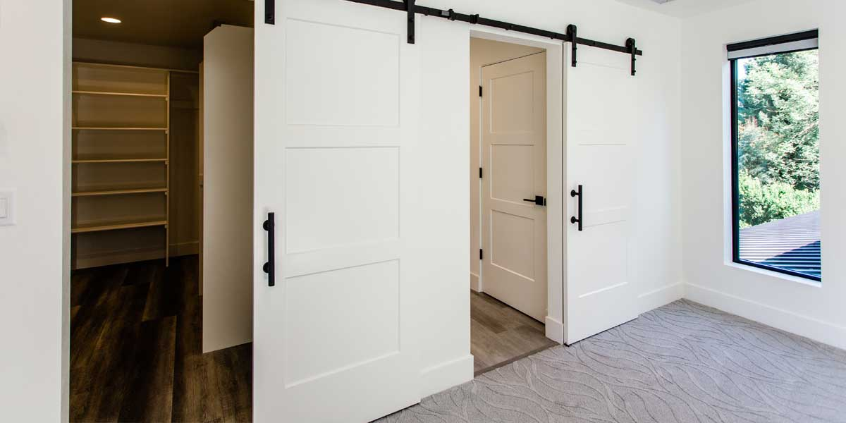 Closet Barn Doors in a Modern Luxury Custom Home by Mike Riddle Construction