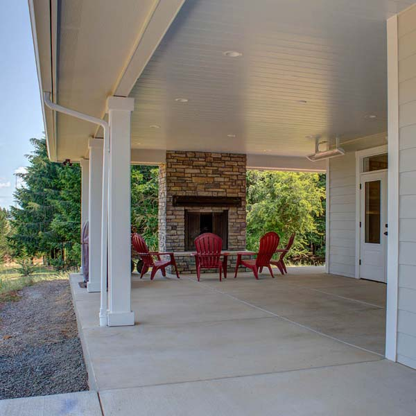 Patio Fireplace in Contemporary Farmhouse by Mike Riddle Construction